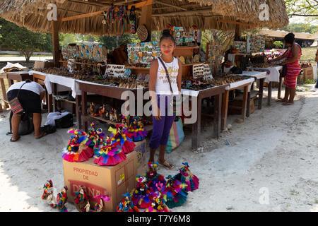 América Central puesto en el mercado adolescente y mujer comerciante vender muñecas y otros artículos artesanales; Tikal, Guatemala América Latina