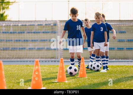 Campamento de fútbol para niños. Niños practican el fútbol regateando en un campo. Los jugadores de fútbol de desarrollar sus habilidades técnicas. Los niños con pelotas y conos de entrenamiento