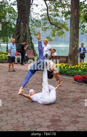Una joven pareja hacer acrobacias en el pavimento del lado del lago Hoan Kiem, en el centro histórico de Hanoi, Vietnam del Norte, el sudeste de Asia Foto de stock