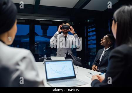 Empresario mirando a través de casco de realidad virtual durante la conferencia en la reunión de mesa