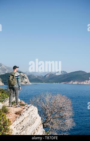Un turista con una mochila en la cima de un acantilado o colina junto al mar se ve en la distancia. Viajar solos.