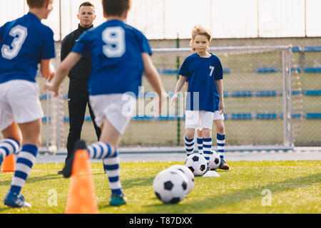 Los niños del fútbol de formación. Los muchachos corriendo con balón en la sesión de práctica de formación. Hacer felices a los niños practicar deportes y divertirse al aire libre