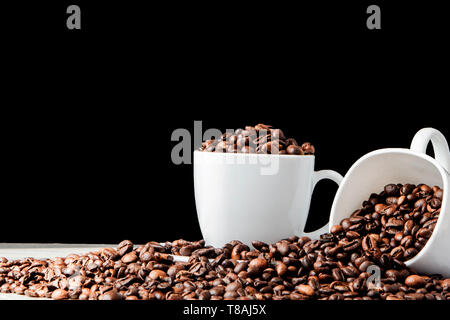 Café Negro en taza blanca y granos de café sobre fondo negro. Vista superior, espacio para el texto