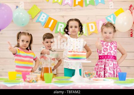 Los niños celebrando la fiesta de cumpleaños. Niños felices, mostrando Thumbs up Foto de stock