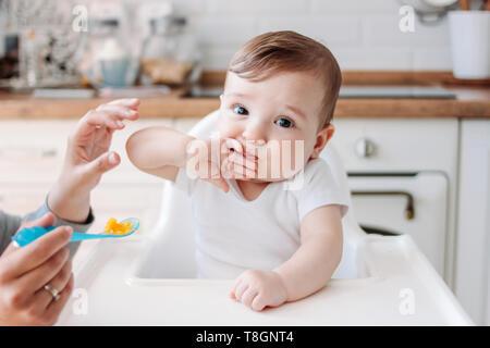 Encantador pequeño baby boy 6-8 meses comiendo alimentos primera calabaza de cuchara en casa