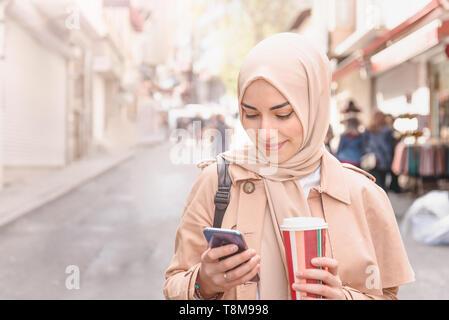 Hermosa mujer musulmana con velo y a la moda con ropa moderna utiliza café para llevar teléfono inteligente mientras camina.Las mujeres musulmanas modernas la vida Foto de stock