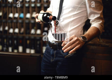 Cerrar Foto recortada. se centran en la botella de vino tinto. ricamente suministrada wine bar en el fondo de la foto.