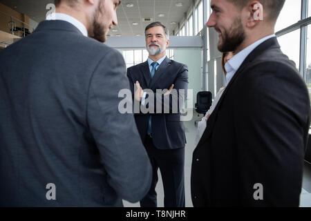 Grupo de gente de negocios ocupada concepto. Equipo empresarial hablar de trabajo en el edificio de oficinas del pasillo.