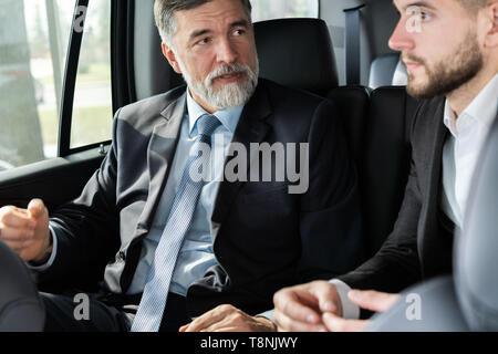 Los compañeros de negocio discutir ideas de negocios mientras está sentado en el asiento trasero del coche o taxi.