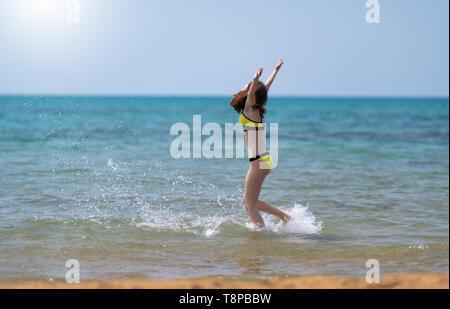 Mujer joven salpicando a través del océano como ella corre a lo largo de una playa de arena en las aguas poco profundas con los brazos levantados en celebración