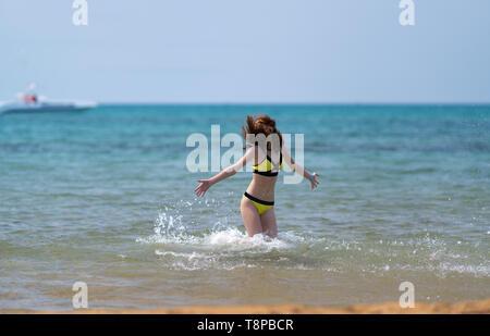 Mujer joven disfrutan de unas vacaciones en el mar corriendo a través de las poco profundas aguas de surf en una playa tropical con los brazos extendidos y el pelo soplando en la