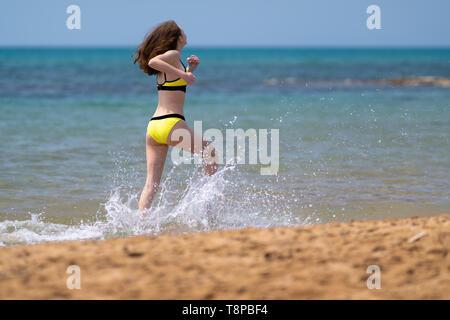 Mujer joven esprinta por la poca profundidad de surf en la playa en un bikini amarillo como ella goza de la libertad de sus vacaciones de verano