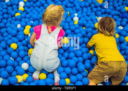 Niños jugando en la piscina de bolas. Coloridos juguetes para niños. Preescolar o kindergarten play room. Niño chico en la guardería infantil interior. Piscina de bolas para
