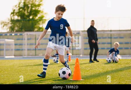 Los niños formación regateando en un campo de fútbol. Niños corriendo la bola. Los jugadores de fútbol de desarrollar sus habilidades técnicas. Los niños entrenamiento con pelotas y conos. S