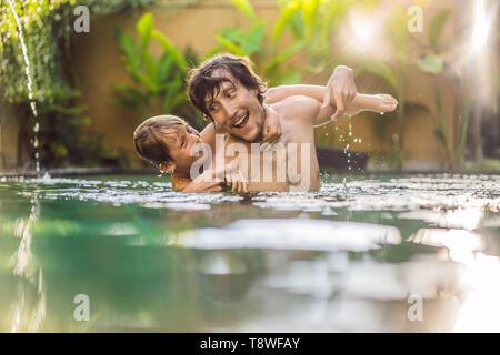 Padre e hijo se divierten en la piscina