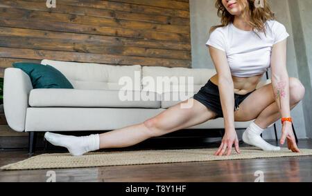 Joven Mujer rubia haciendo yoga ejercicios de estiramiento en casa. Estilo de vida saludable.