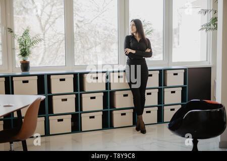 Mujer de negocios sonriendo de pie con los brazos cruzados en la oficina. Mujer de vestimenta formal de negocios de pie delante de su escritorio en la oficina. Foto de stock