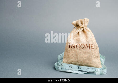 Bolsa de dinero con la palabra ingresos y cinta métrica. La reducción de los ingresos y beneficios. Presupuesto reducido. Pérdida de dinero. Negocios infructuosos y la pobreza. Lowe