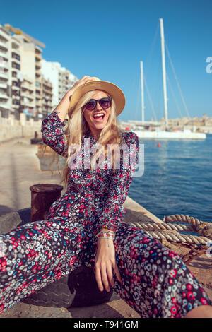 Feliz moda mujer mediterránea en hat riendo en puerto dock