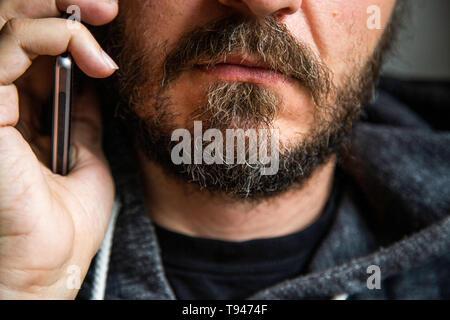 Cerrar retrato del hombre barbado hablando por teléfono inteligente, se centran en los labios, sin ojos, secreto hablar, alguien dañinas penal