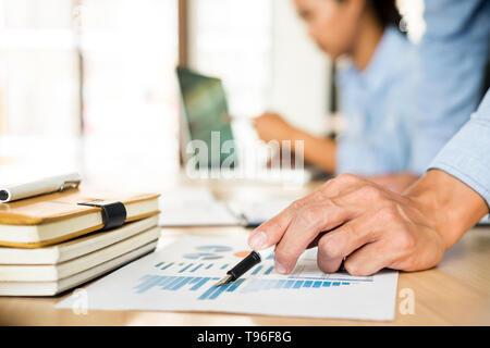 Equipo empresarial manos a trabajar con plan de despacho y moderno equipo digital portátil. Inspector financiero del administrador y secretario haciendo rep Foto de stock