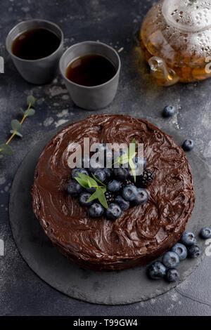 Tarta de chocolate con tetera y tazas sobre fondo oscuro. Vista lateral, concepto de celebrar la comida de vacaciones