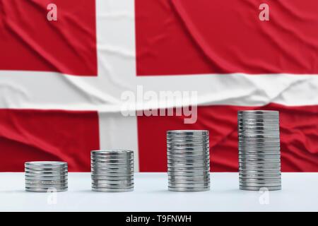 Pabellón de Dinamarca arrugado en el fondo con filas de monedas para financiar y concepto de negocio. Ahorro de dinero.
