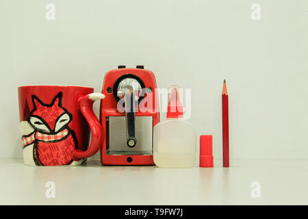 Sacapuntas rojo máquina con taza y pegamento sobre fondo blanco.