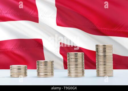 Dinamarca ondear la bandera en el fondo con filas de monedas para financiar y concepto de negocio. Ahorro de dinero.