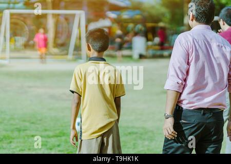 Los niños asiáticos práctica pateando la pelota para marcar goles en el campo de fútbol del público.