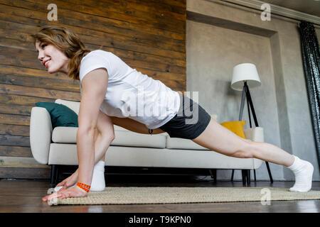 Joven Mujer rubia haciendo yoga ejercicios de estiramiento en casa. Estilo de vida saludable. Relajación y bienestar. Armonía con sí mismo.