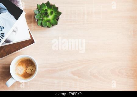 Vista superior de libros y revistas, una taza de café y plantas suculentas sobre fondo de madera. Copie el espacio. Concepto de tiempo y espacio de recreo.