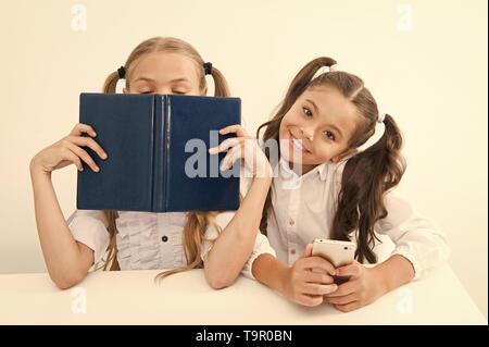 Contra la vieja escuela moderna. Colegiala mantenga teléfono móvil smartphone moderno mientras su amiga disfrute de libro viejo como almacenamiento de datos analógicos. Tecnología contra e