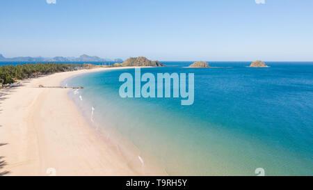 Vista aérea de la isla tropical con playas de arena y palmeras. La Isla de Malajon, Filipinas, Palawan. embarcaciones turísticas en la costa tropical de la isla. Concepto de vacaciones de verano y viajes. la playa y el agua del mar azul claro