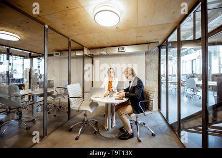 Hombre y mujer de negocios que trabajan en la sala de reuniones, amplia vista desde el interior de la habitación con tabiques transparentes