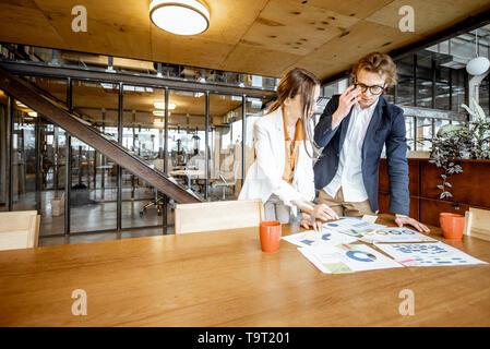 Joven Hombre y mujer de negocios trabajando en documentos en la mesa de madera en la oficina o espacio de coworking