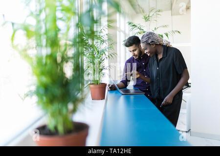 Socios de negocio trabajando en el portátil en la oficina moderna