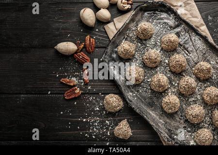 Placa con sabrosos dulces trufas en mesa de madera oscura
