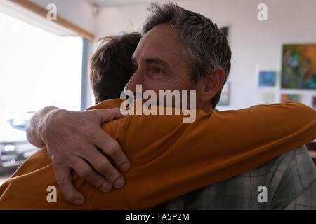 Padre e hijo abrazándose entre otros