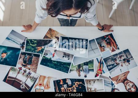Vista superior de una hembra, fotógrafo que trabaja en studio mirando las impresiones acostado sobre el escritorio. Fotógrafo hembra elegir la mejor imagen desde varios phot