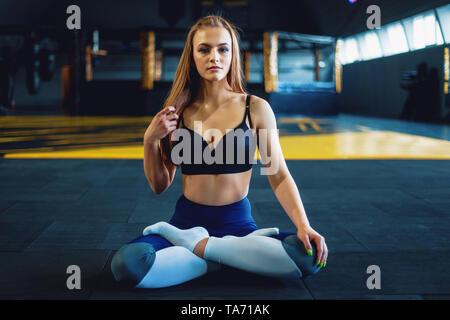 Estirando el gimnasta chica hacer yoga exersizes. Vista del atractivo joven haciendo lotus plantean