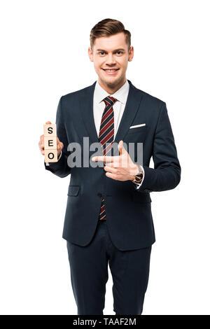 Vista recortada de feliz empresario apuntando con el dedo a cubos de madera con letras seo aislado en blanco