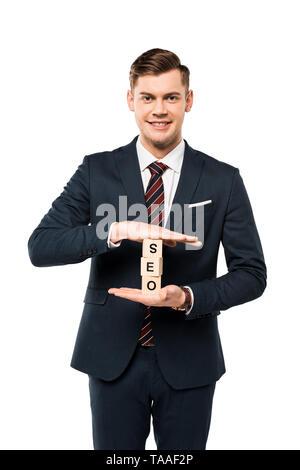 Empresario feliz celebración cubos de madera con letras seo aislado en blanco