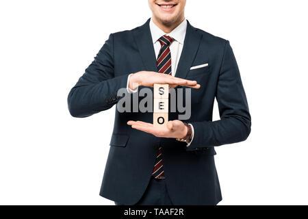 Vista recortada del empresario feliz celebración cubos de madera con letras seo aislado en blanco