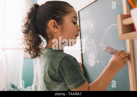 Niña dibujando con una tiza en la pizarra en su habitación de la casa, espacio para copiar texto