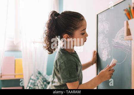 Niña dibujando con una tiza en la pizarra de su habitación en la casa, espacio para copiar texto