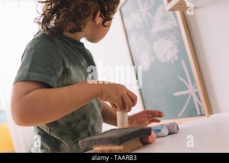 Niña mirando su dibujo en la pizarra en su habitación de la casa, espacio para copiar texto