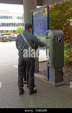 El hombre compra un ticket de aparcamiento de pago automatizado máquina al Hospital General de Richmond, Richmond, BC, Canadá
