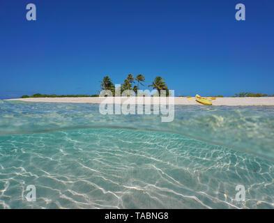 Isla tropical de arena con un kayak de mar en la playa de arena y submarinas, Polinesia francesa, Océano Pacífico, vista dividida por la mitad y bajo el agua.