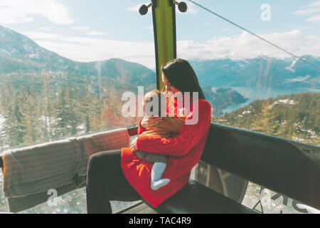 La madre sostiene a su hijo en la góndola de un teleférico, Squamish, Canadá